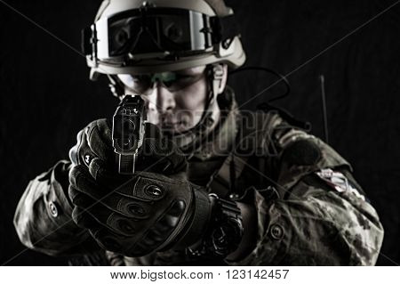 Young handsome military man in italian camouflage aiming from handgun he wearing helmet glasses and radio set. Focus on the gun muzzle