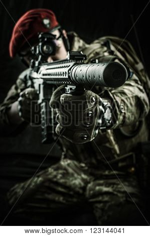 Young handsome military man in italian camouflage aiming from automatic rifle he wearing red beret and gloves. Focus on the gun muzzle