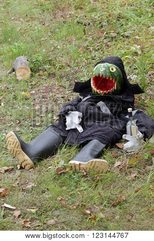 close-up of a scarecrow in a jacket and boots in a meadow made of watermelon