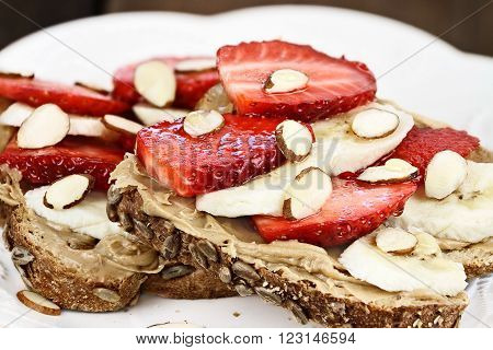 Healthy wholefoods breakfast of whole grain toast peanut butter bananas fresh strawberries almonds and honey.