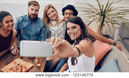 Multiracial people enjoying in party taking a self portrait with mobile phone. Group of young friends sitting on couch taking selfie with smart phone on roof top.