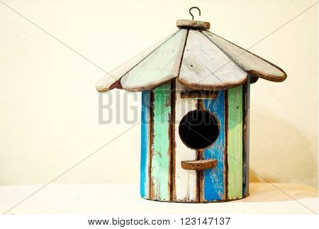 Old wooden birdhouse in green blue and white surrounded by cobweb and spiderweb/Old wooden birdhouse in colorful color