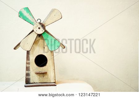 Old wooden birdhouse in windmill shape surrounded by cobweb and spiderweb/Old wooden birdhouse in windmill shape