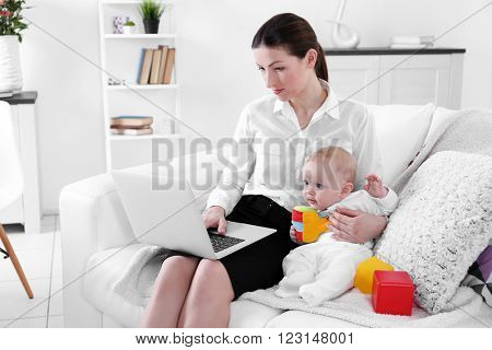 Businesswoman with baby boy on couch working from home using laptop