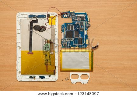 Disassembled Computer Tablet On Wooden Background. View From Above.