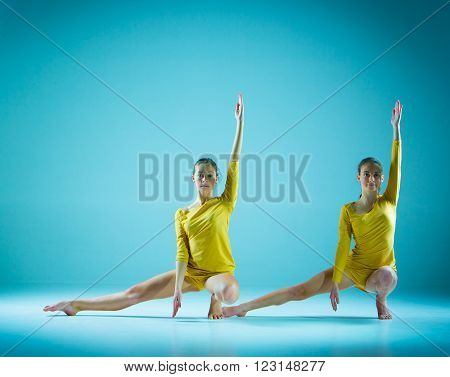 The two modern ballet dancers dancing on gray background