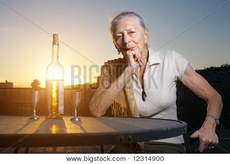 Elderly Woman Sitting At The Table Outdoors At Sunset.