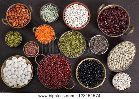 Beans peas and lentils in metal bowls.