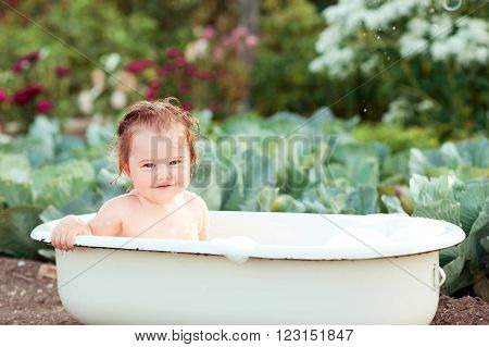 Smiling baby girl sitting in bath. Washing outdoors. Playing. Childhood.