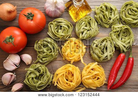 Raw tagliatelle pasta on the wooden table.