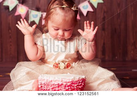 Baby girl sitting on wooden floor with birthday cake in room. First birthday. Celebration.