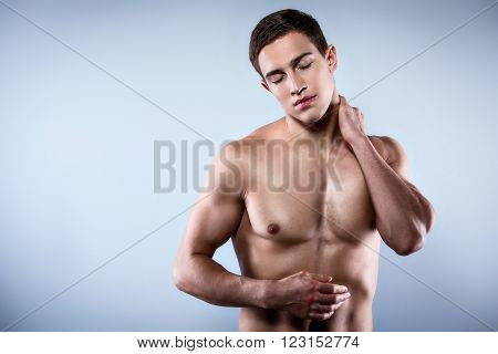 Studio shot of handsome young man with naked torso. Man suffering from body ache