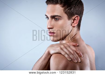 Studio shot of handsome young man with naked torso. Man suffering from shoulder ache