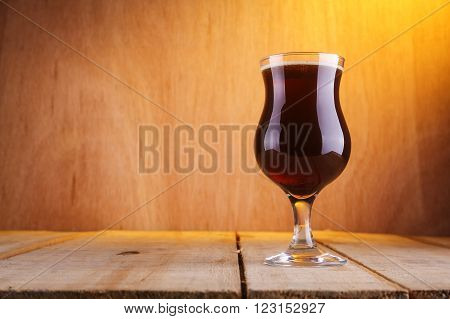 Tall tulip glass with dark brown beer on a grunge wood surface