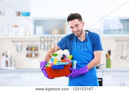 Man holding plastic basin with brushes, gloves and detergents in the kitchen