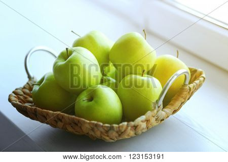 Ripe green apples in a wicker basket on windowsill