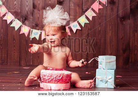 Baby girl 1 year old eating birthday cake over wooden background. Smiling child with birthday decorations in room. Happy birthday. Celebration. Childhood.