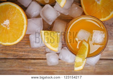 Orange juice with cubes of ice and orange on wooden table background, closeup