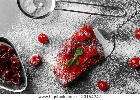 Delicious powdered cherry strudel with mint on shovel