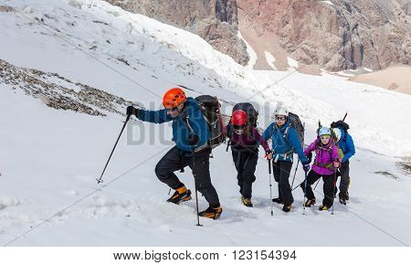Large group of tourists of different sex ethnic nation race age young and old man woman walking difficult Snow terrain Steep Mountain Landscape in Background