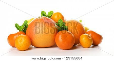 A heap of mixed citrus fruit including a grapefruit, oranges, lemons, clementines, tangerines with mint sprigs isolated on a white background, close up