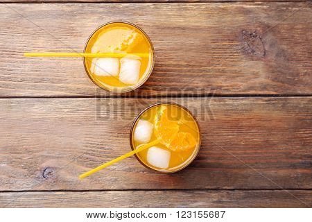 Glasses of orange juice with ice blocks and tubule on wooden background