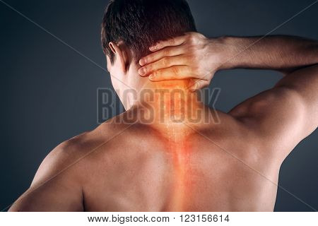 Studio shot of handsome young man with naked torso. Man suffering from neck ache. Red spot on neck