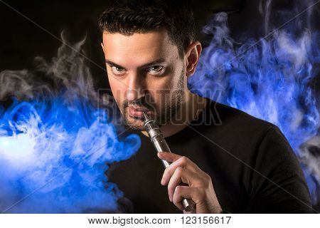 Black haired handsome man with e-cirarette in a blue lighted vapor