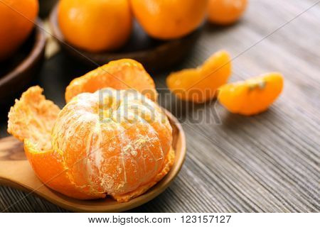 Fresh delicious peeled and unpeeled tangerines on the spoon with slices on the wooden table, close up