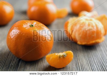 Fresh delicious unpeeled and peeled tangerines with slices on the wooden table, close up