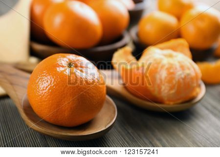 Fresh delicious peeled and unpeeled  tangerines on the wooden spoons, close up