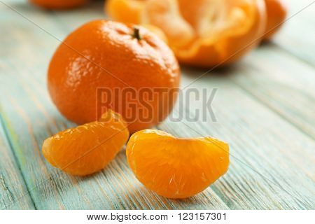 Fresh delicious unpeeled tangerines and peeled with slices on the light-blue wooden board, close up