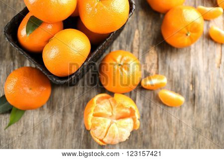 Fresh, delicious peeled and unpeeled tangerines with slices beside full wicker basket of mandarins on the rustic table, top view