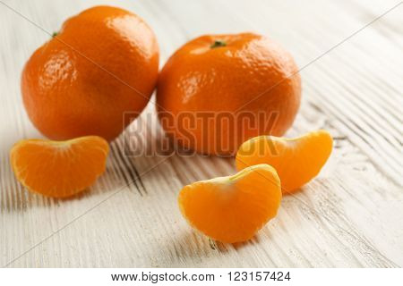 Two fresh delicious unpeeled tangerines with slices on the white wooden table, close up