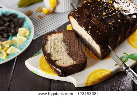 Composition of tasty cake with chocolate morsels and pieces of lemon on dark wooden background