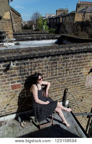 Girl in black polka dot dress and sunglasses sitting on the balcony of the second floor of a house in London. She takes sun baths in the spring.