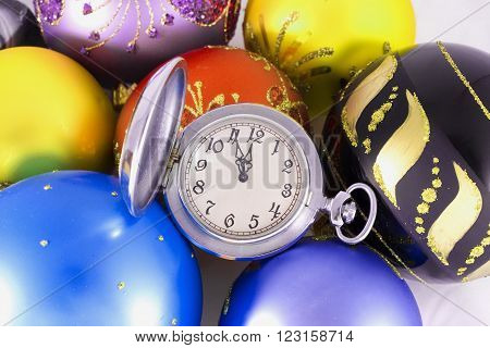 Pocket watch showing almost twelve o'clock and Christmas balls