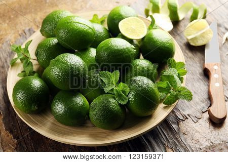 Limes and zest on wooden table