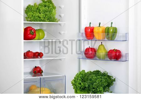 Open fridge with fresh fruits and vegetables in the kitchen
