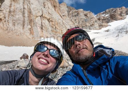 Faces of Smiling Man and Woman Sport Style Clothing Protection Helmets Sunglasses High Altitude Mountain Landscape with Rock and Snow on Background