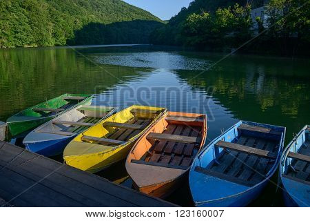 Lillafured is a popular tourist resort in Bukk Mountains (Hungary). Multicolored boat for rent in foreground. Location - Hamori lake.