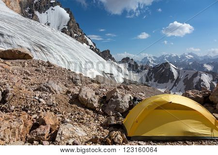 Mountain View with Ice Glacier and Peaks on Background and Small Single Alpine Yellow Tent located on Rocky Moraine on Foreground