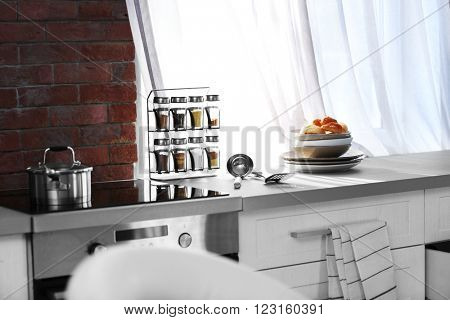 Modern kitchen table with electric stove and utensils beside the window