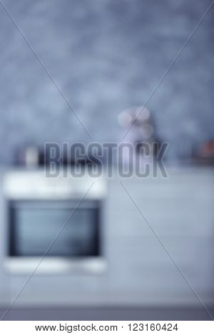 Blurred modern kitchen interior with light furniture and electric stove