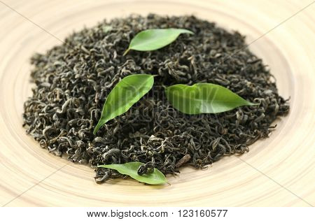 Dry tea with green leaves in beige plate, closeup