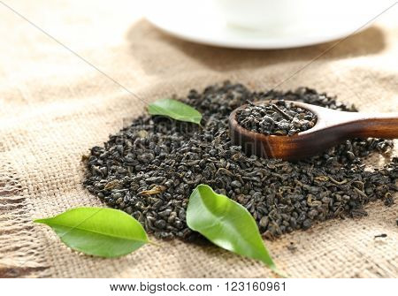 Dry tea with green leaves on burlap background