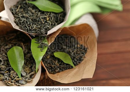Dry tea with green leaves in cornets on wooden table background