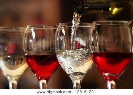 White wine pouring into wine glass, closeup