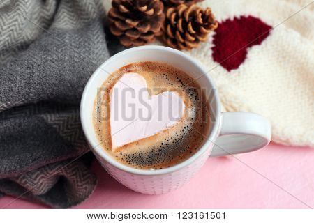 Cup of hot cappuccino with heart marshmallow and warm clothes on pink background, close up