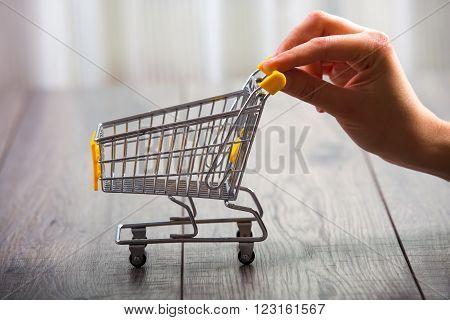 Hand push the shopping cart, wooden background